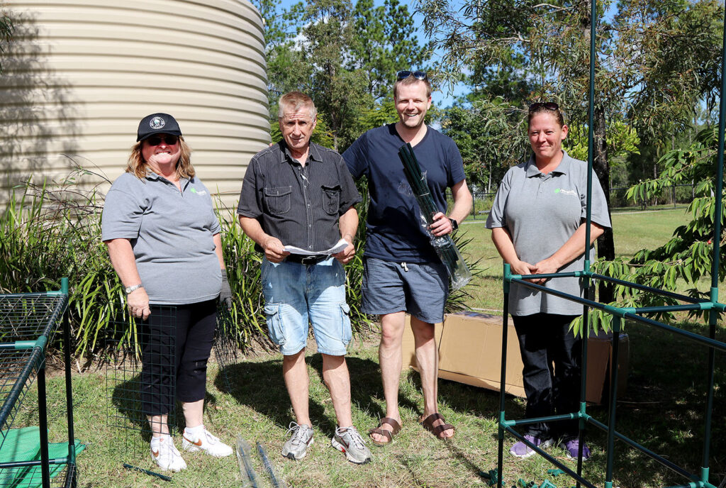Volunteers build a greenhouse at the Gardens